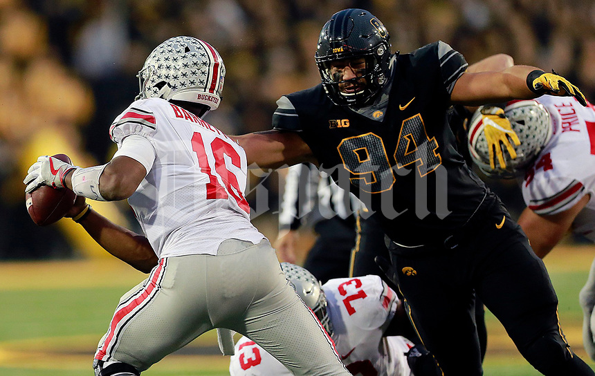 Ohio State Buckeyes quarterback J.T. Barrett (16) avoids a tackle by Iowa Hawkeyes defensive end A.J. Epenesa (94) in the second half of their game at Kinnick Stadium in Davenport, IA on November 4, 2017. [ Brooke LaValley / Dispatch ]