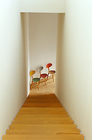 Three brightly-coloured retro chairs add a vivid note at the base of the staircase