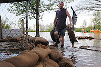 Family friend Ryan Hallam sandbags the backyard of 1207 North Main Street in order to protect the home from four feet of Mississippi River floodwater in the Red Star District of Cape Girardeau, MO, on Thursday, April 28, 2011.