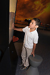 Oakland CA 2nd grade boy studying model of the interior of a volcano at the Chabot Space and Sciene Center