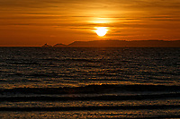 The sun is seen setting over Mumbles Head near Swansea, from the nearby beach of Aberavon in south Wales, UK. Wednesday 24 October 2018