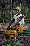 "Jennifer Thomas waters a community vegetable garden in Captain, a village in southern Malawi that has been hard hit by drought in recent years, leading to chronic food insecurity, especially during the ""hunger season,"" when farmers are waiting for the harvest. The ACT Alliance is working with farmers in this village to switch to alternative, drought-resistant crops, such as millet, as well as using irrigation and other improved techniques to increase agricultural yields. In Captain, the ACT Alliance helped the community install solar-powered pumps that fill a reservoir, which in nturn provides water for the irrigation system."