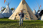 A young cowboy with his lasso poses for a picture in The Indian Village Teepees at the Pendleton Round Up, Pendleton, Oregon, USA