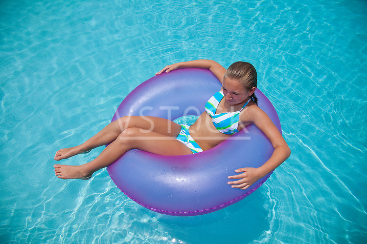 USA, Florida, St. Petersburg, girl (12-13) floating on water in inflatable tube