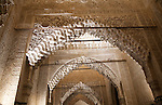Illuminated view at night of richly decorated Islamic stonework arch Alhmabra palaces, Granada, Spain