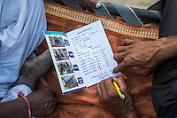 Technoserve's Field Extension Officer, Surender Singh, collects data and feedback from guar farmer Bhanwarlal Sharma, 60, at his farmhouse in Bamanwali village, Bikaner, Rajasthan, India on October 24th, 2016. Non-profit organisation Technoserve works with farmers in Bikaner, providing technical support and training, causing increased yield from implementation of good agricultural practices as well as a switch to using better grains better suited to the given climate. Photograph by Suzanne Lee for Technoserve