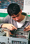 Teenager male intern working computer parts salvaging repairing vertical