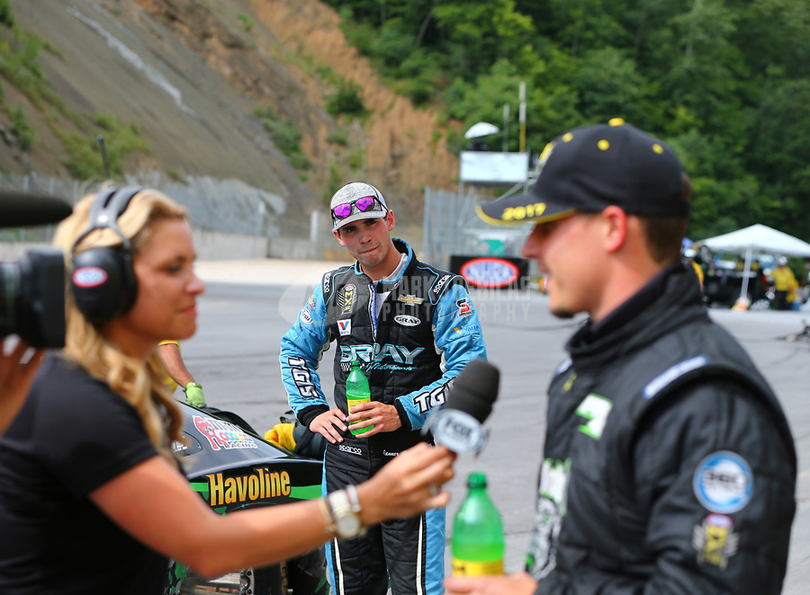 Jun 18, 2017; Bristol, TN, USA; Tanner Gray (center) looks on as NHRA pro stock driver Alex Laughlin is interviewed after defeating him during the Thunder Valley Nationals at Bristol Dragway. Mandatory Credit: Mark J. Rebilas-USA TODAY Sports