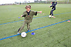 Boys practicing kicking a football on a playing field at their local leisure centre,