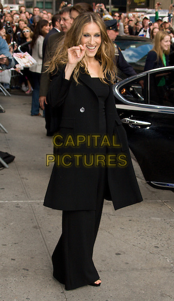 "SARAH JESSICA PARKER.Appearance on the ""Late Show with David Letterman"" at the Ed Sullivan Theater, New York, NY, USA..May 22nd, 2008.SJP full length black coat jacket top trousers wide leg catsuit jumpsuit hands in pockets hand waving .CAP/LNC/TOM.©TOM/LNC/Capital Pictures."