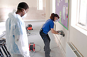 Premises staff refurbishing a room watched for the moment by a Work Experience student,  State Secondary Roman Catholic school.