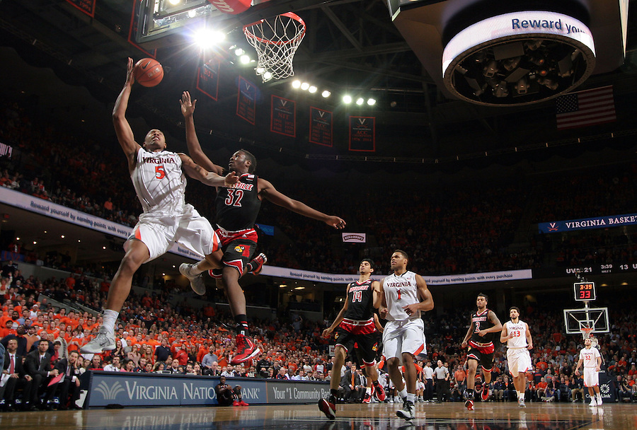 Virginia forward Darion Atkins (5) shoots next to Louisville forward/center Chinanu Onuaku (32) during the game Saturday Feb. 7, 2015, in Charlottesville, Va. Virginia defeated Louisville  52-47. (Photo/Andrew Shurtleff)