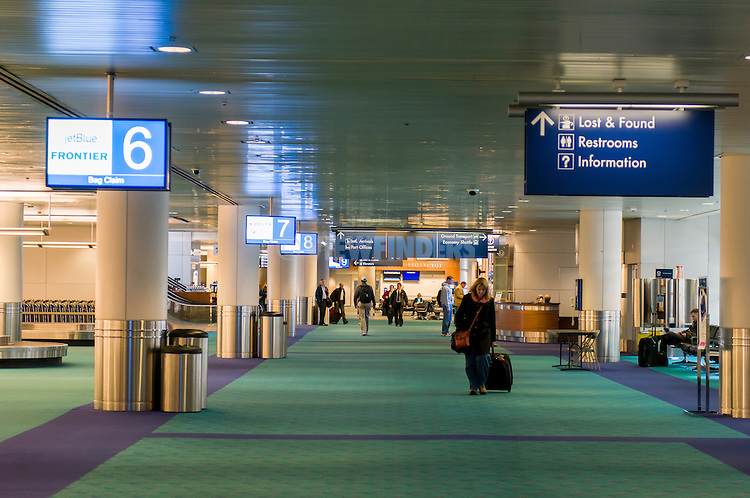 Interior view at the Portland International Airport with wall boards and signage.
