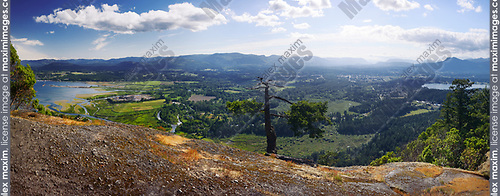 Panorama of North Cowichan Valley, Genoa Bay, aerial nature scenery with mountains in the background from a hill top lookout. North Cowichan, Vancouver Island, British Columbia, Canada