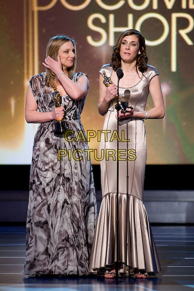 VANESSA ROTH & CYNTHIA WADE.Accept the Academy Award for Best Documentary Short during the 80th Annual Academy Awards at the Kodak Theatre in Hollywood, California, USA..February 24th, 2008.oscars full length microphone speech dress trophy winner beige cream silk satin pattern print .CAP/A.M.P.A.S./AW.Supplied by AW/A.M.P.A.S./Capital Pictures.