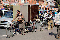 Jaipur, Rajasthan, India.  Mid-day Street Traffic in Central Jaipur.  Man Hauling Large Cabinets on a Three-wheeled Bicycle-cart Makes his Way through Mid-Day Traffic.