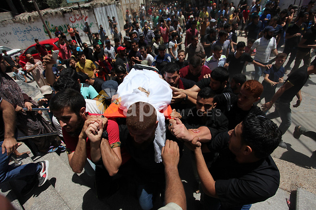 Palestinian relatives carry the body of Yussef al-Faseeh, 29, who was shot dead by Israeli troops during clashes at Israel-Gaza border, during his funeral in Gaza city on on 9, 2018. Four Palestinians were killed by Israeli fire on the Gaza border on June 8, the territory's health ministry said giving a new toll, as weeks of deadly clashes with protesters continued. Photo by Mahmoud Ajour