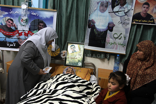 The mother of Palestinian prisoner Fahmi Abu Salah, stands next to her son wife as she lies in a hospital bed after she gave birth to a baby boy conceived with Abu Salah's sperm smuggled out of an Israeli prison in Gaza City January 23, 2014.  May, the Gaza wife of a Palestinian prisoner in an Israeli jail, gave birth to her baby boy on Thursday in the second successful smuggling of sperm to lead to a pregnancy in the embattled coastal enclave. Photo by Mohammed Asad