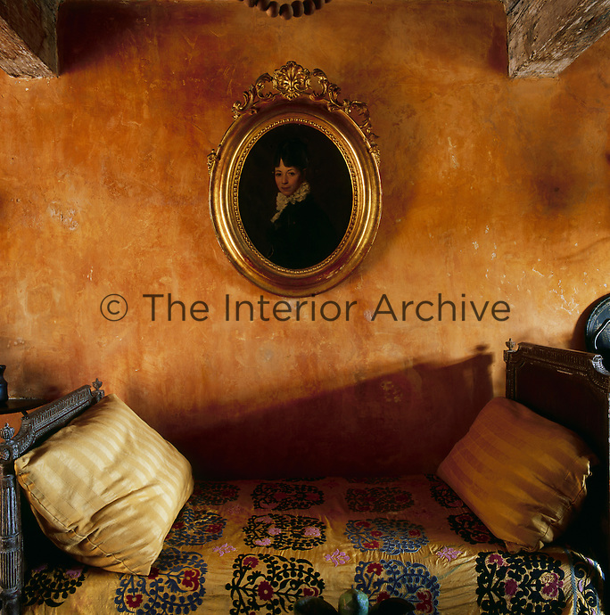 A rustic sitting room with stone walls painted natural pigments inspired by the colours of Provence, such as yellow ochre, while being careful to leave the original underlying layers. A period portrait painting hangs on the wall above an antique daybed with a patterned cover.