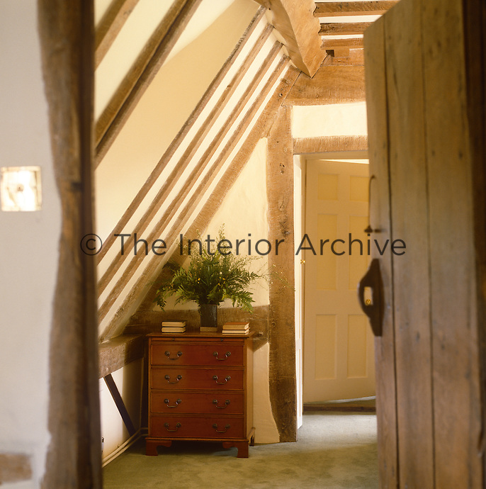 A wooden door leads through to an upstairs room situated under the eaves of the cottage