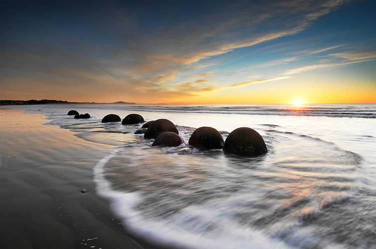 A line of Moeraki Boulders is silhouetted as the sun rises above the horizon, Coastal Otago, South Island, New Zealand - stock photo, canvas, fine art print