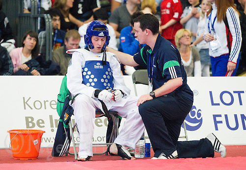 05 MAY 2012 - MANCHESTER, GBR - Conor Grassick (IRL) of Ireland listens to his coach during the men's -63kg category second round contest against Mario Silva of Portugal during the 2012 European Taekwondo Championships at Sportcity in Manchester, Great Britain (PHOTO (C) 2012 NIGEL FARROW)