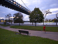 "USA. New York City. Queens. Astoria park. The Robert F. Kennedy (RFK) Bridge, formerly known as the Triborough Bridge (sometimes spelled Triboro Bridge), is a complex of three separate bridges. Spanning the Harlem River, the Bronx Kill, and the Hell Gate (part of the East River), the bridges connect the boroughs of Manhattan, Queens, and The Bronx via Randall's Island and Wards Island, which are joined by landfill. Often still referred to as simply the ""Triboro"" the spans were officially named after Robert F. Kennedy in 2008. Night view on the Hudson river.  A man does his jogging. 21.10.2011 © 2011 Didier Ruef"