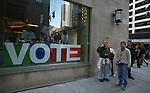 "People stand next to a window with the sign ""vote"" in Chicago, Friday Oct 10 2008. Americans will go to the polls on Nov 4, at a time of great Financial crisis, war in Iraq and Afghanistan, to elect a  new President. A vote, that will affect not only America, but the whole world. Photo by Eyal Warshavsky ."