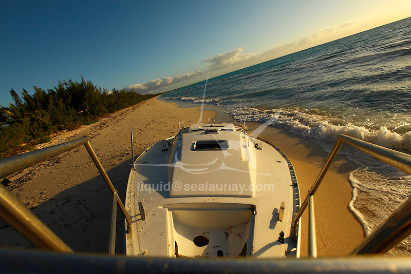 "The wreck of a Beneteau sailing yacht full of sand on the Fayaoue beach on the Ouvea island in the Loyalty islands..Ouvéa (local pronunciation: [u?ve.a]) is a commune in the Loyalty Islands Province of New Caledonia, an overseas territory of France in the Pacific Ocean. The settlement of Fayaoué [fa?jawe], on Ouvéa Island, is the administrative centre of the commune of Ouvéa..Ouvéa is made up of Ouvéa Island, the smaller Mouli Island and Faiava Island, and several islets around these three islands. All these lie among the Loyalty Islands, to the northeast of New Caledonia's mainland..Ouvéa Island is one of the Loyalty Islands, in the archipelago of New Caledonia, an overseas territory of France in the Pacific Ocean. The island is part of the commune (municipality) of Ouvéa, in the Islands Province of New Caledonia..The crescent-shaped island, which belongs to a larger atoll, is 50 km (30 miles) long and 7 km (4.5 miles) wide. It lies northeast of Grande Terre, New Caledonia's mainland..Ouvéa is home to around 3,000 people that are organized into tribes divided into Polenesian, Melanesian and Walisian by ethnic descend. The Iaai language is spoken on the island..The two native languages of Ouvéa are the Melanesian Iaai and the Polynesian Faga Uvea, which is the only Polynesian language that has taken root in New Caledonia. Speakers of Faga Uvea have fully integrated into the Kanak society, and consider themselves Kanak..Ouvéa has rich marine resources and is home to many sea turtles, species of fish, coral as well as a native parrot, the Uvea Parakeet, that can only be found on the island of Ouvéa..A large crustacaen called a ""coconut crab"" or crabe de cocotier can also be found on the islands. The large crabs live in palm tree plantations and live solely on a diet of coconuts that they crack open with their powerful claws. They are blue in colour and can grow to several kilos in size. They are a land based species and do not venture into the ocean.."