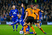 Kenneth Zohore of Cardiff City falls under pressure from Romain Saiss and Ryan Bennett of Wolverhampton Wanderers during the Sky Bet Championship match between Cardiff City and Wolverhampton Wanderers at the Cardiff City Stadium, Cardiff, Wales on 6 April 2018. Photo by Mark  Hawkins / PRiME Media Images.