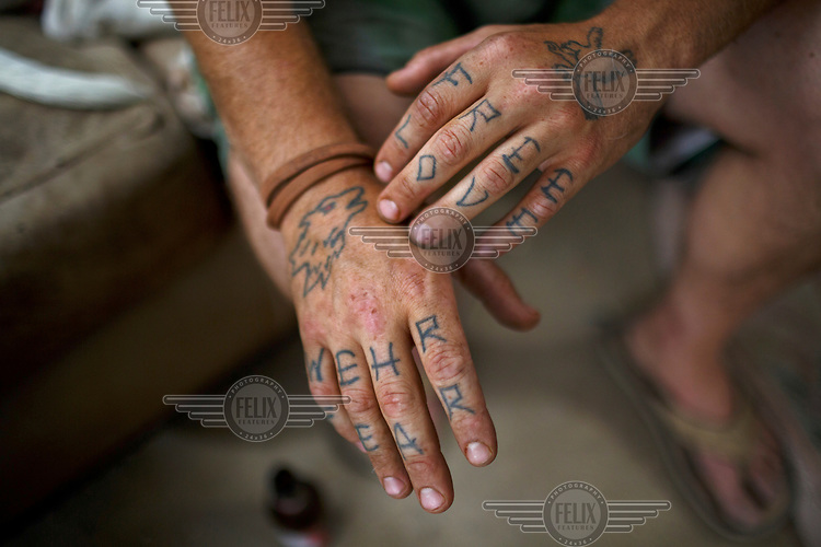 Mike, a resident of Slab City, a squatters' camp about 190 miles southeast of Los Angeles, reveals his tattooed hands. Each design represents different phases of his growth.  <br /> <br /> Slab City, known as The Slabs, is named for its areas of concrete where for many years, since the military based closed, people have parked their RVs as they travel south for the winter. There is also a permanent community of 'Slabbers', around 200 people, who have established themselves living free in the Sonoran Desert where temperatures can reach 48 Celsius in the summer and, while there is no rent, there is also no water, electricity or services. Slabbers are an eclectic bunch often escaping poverty but also holding in common the desire to escape the rules and order of society in what they like to call 'the last free place on earth'.