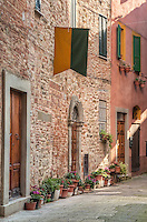 The very narrow Via Virgillo Ceppari leads off the Piazza Grande inside the eastern gate of the pretty walled hill town of Panicale, just south of Lake Trasimeno. Entered through a dark archway this little street is attractively lined with pot plants. The pennant may represent a local ward or district in the town, like the famous contrade of Siena, or it may just be decorative. Capturing a scene such as this, with a huge dynamic range in the lighting, is a real challenge and this shot required several different exposures to be merged together, using a technique known as 'exposure fusion'.