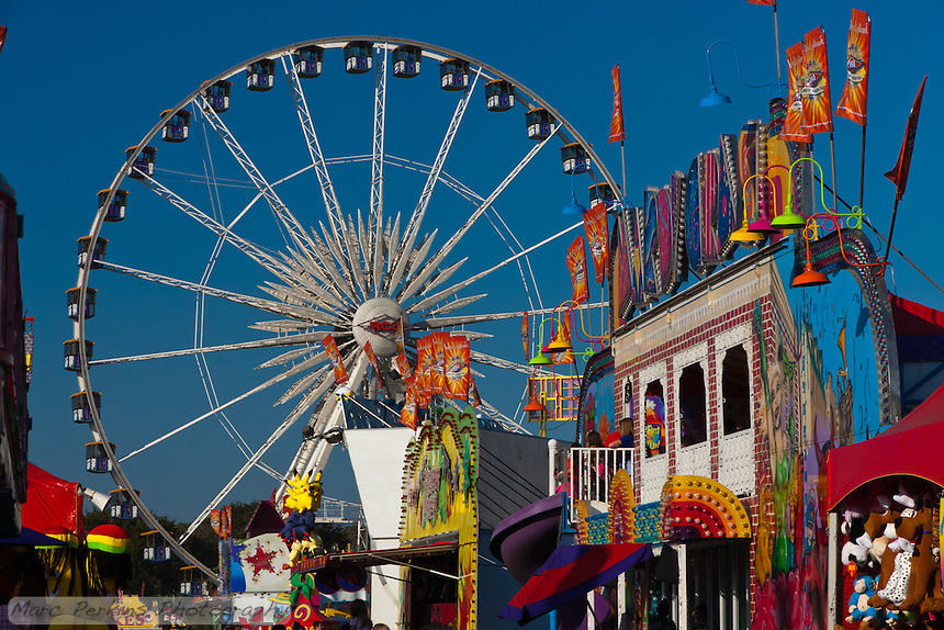 Carnival rides in front of the the Orange County Fairground's RCS ferris wheel.