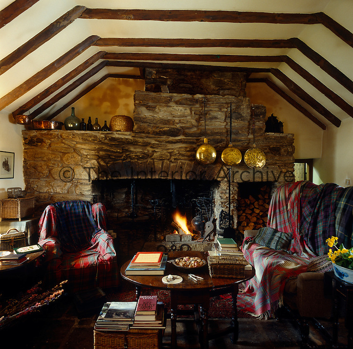 Tartan blankets are used as throws to cover the furniture in this snug sitting room