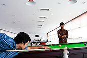 Gaureesh Dubey (right) looks on while Devasheesh Dubey hits the ball on the pool table at the recreation hall of Jindal Global University in Sonipat, Haryana, India Photograph: Sanjit Das/Panos