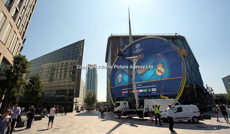 Pictured: Workers secure a giant UEFA Champions League banner outside St Davids Centre the Library building in The Hayes, Cardiff. Thursday 25 May 2017<br />Re: Preparations for the UEFA Champions League final, between Real Madrid and Juventus in Cardiff, Wales, UK.