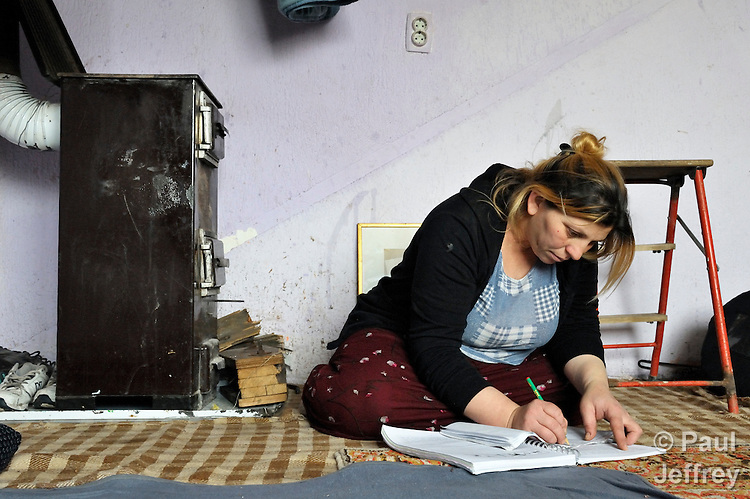 "THIS PHOTO IS AVAILABLE AS A PRINT OR FOR PERSONAL USE. CLICK ON ""ADD TO CART"" TO SEE PRICING OPTIONS.   Giltena Duda studies for her basic literacy class in her home in the Zemun Polje Roma neighborhood of Belgrade, Serbia. Ms. Duda is pregnant with her seventh child. She and her husband are Roma refugees from Kosovo, and thus legally marginalized in Serbia. They built their home on unregistered land and pirate their electrical hookup. Without legal residency, their children can't attend a regular school, and they have difficulties getting formal employment. Yet both adults participate in a literacy program sponsored by the Branko Pesic School, where their children attend classes. The school is supported by Church World Service."