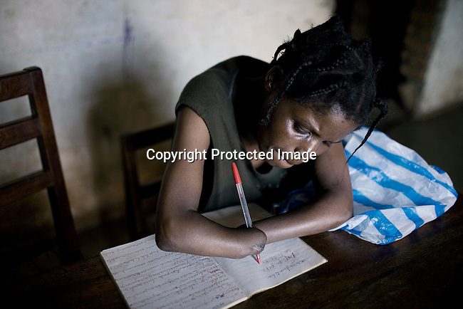 BUKAVU, DEMOCRATIC REPUBLIC OF CONGO - OCTOBER 30: Woman writes notes in a book in her small house in Bukavu, DRC. She was abducted, held captive and raped by rebels in the DRC conflict. Her hands were amputated before she was finally released. She lives with her husband and four children, which is quite unusual, as many men abandon their wives or daughters if they have been raped. The DRC conflict has seen an unprecedented high rate of rape and sexual abuse of women. The culprits are both different rebel groups and government soldiers and very few are punished. About 27,000 sexual assaults were reported in South Kivu province alone in 2006, according to the United Nations. (Photo by: Per-Anders Pettersson)