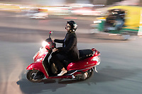 A person drives a scooter in traffic at night near HUDA City Centre in Gurugram, Haryana, India, on Mon., December 10, 2018.