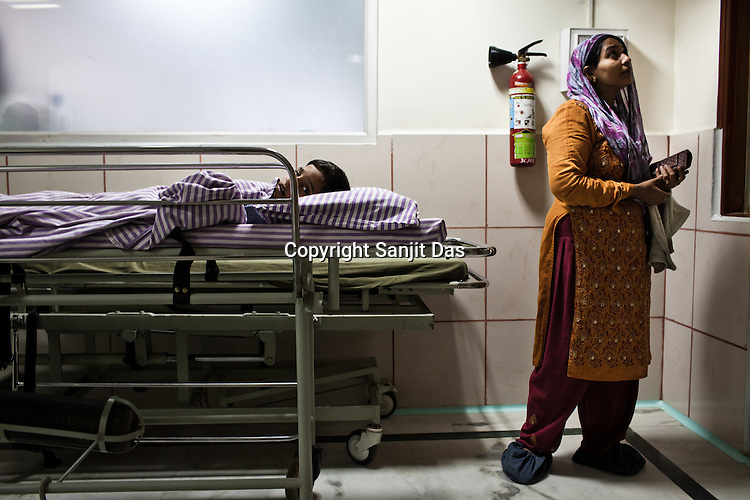 An woman gets emotional as her son lies on the stretcher waiting to be taken to the Operation Theatre of the Narayana Hrudayalaya in Bangalore, Karnataka, India. Photo: Sanjit Das/Panos