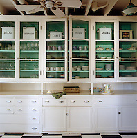 Old fashioned white tins line the top of the shelves in the butler's pantry painted in Benjamin Moore South Beach.