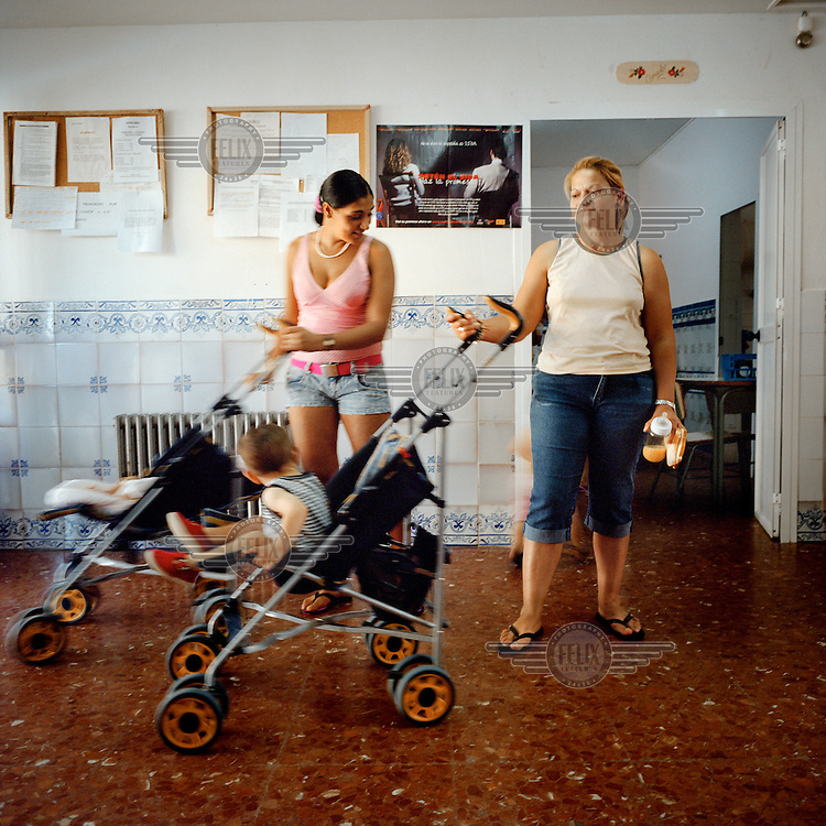 Two inmates with their children at Alcala de Guadaira prison. More than 200 women live with their children in Spanish jails. Children can live with their mothers in prison up to the age of three.