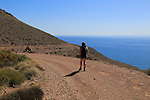Woman walking along coast path in Cabo de Gata national park, near San José, Almeria, Spain