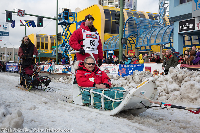 Aaron Burmeister and team leave the ceremonial start line with an Iditarider at 4th Avenue and D street in downtown Anchorage, Alaska during the 2015 Iditarod race. Photo by Jim Kohl/IditarodPhotos.com