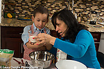 3 year old boy in kitchen at home with mother learning to cook baking, looking at level of milk in measuring cup