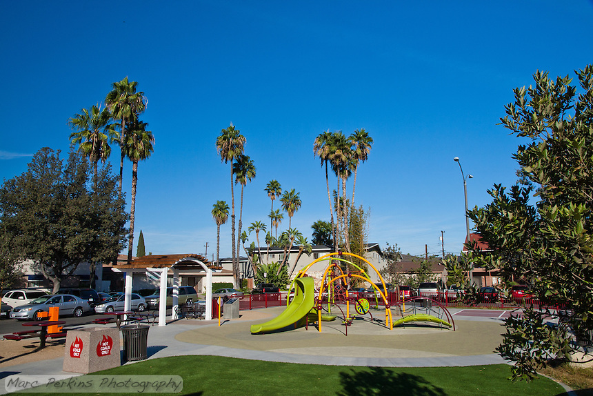 An overview of Circle Park, a pocket park located on Park Circle Drive in Anaheim, California.  This is a relatively wide-angle view of the park that places the park in the context of its surrounding parking and apartments.  Visible are play structures, an artificial-turf lawn, a picnic / BBQ area, a red fence, and more.