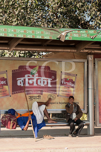 Delhi, India. Sikh Warrior resting at a bus stop with an advertisement for Vernika Gold Supari betel (areca) nut mouth freshener, a non-tobacco carcinogen. The advertisement carries a health warning.