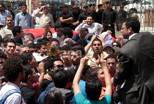 """Egyptian members of 6th April movement celebrate the releasing of four members of the movement in front of Attorney General's Office in Cairo on April 29, 2013. Three of the group's members and one other protester have been detained following a demonstration against police violence outside the residence of Egypt's interior minister in late March. They were arrested for chanting against the interior ministry and describing it as a """"prostitute"""". Photo by Tareq Gabas"""