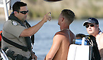 Officer Charlie Malono, left, with the Florida Fish and Wildlife Commission performs a field sobriety test on a boater suspected of boating under the influence in the mouth of the Carrabelle River Memorial Day weekend. The sobriety checks were at the end of the White Trash Bash on Dog Island off the coast of Carrabelle, Florida May 27, 2007.   Fourty law enforcement officers from four different agencies made 10 arrests for boating under the influence.