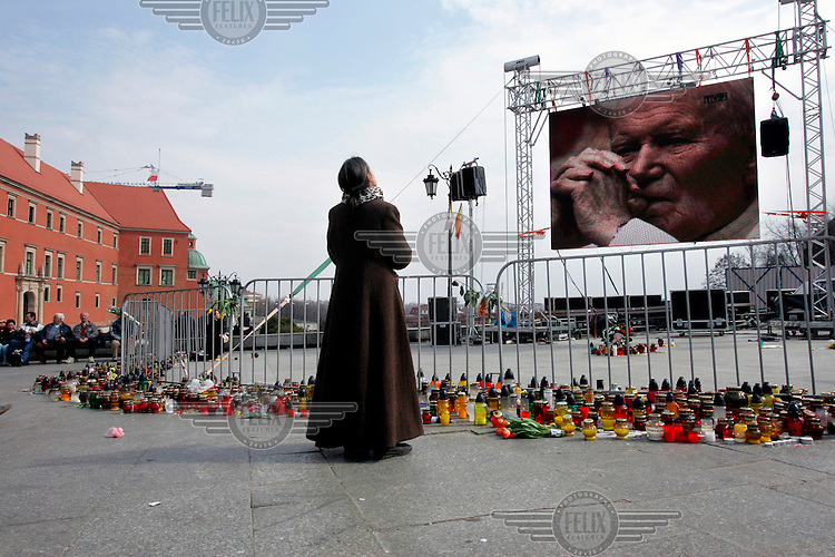 A woman prays after watching a live transmission of the funeral of Pope John Paul II. Millions of Poles turned out to honour their countryman.